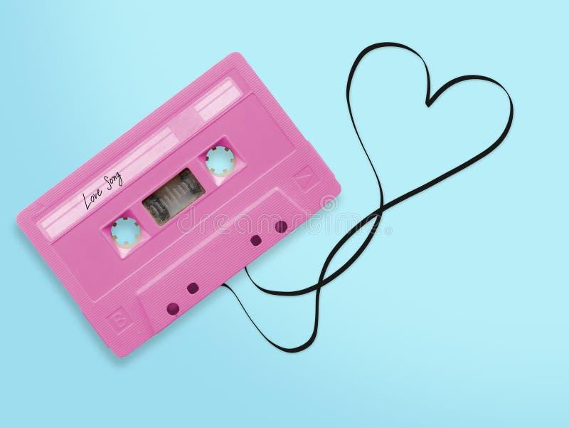Ρόδινη ακουστική ταινία κασετών με την μπλεγμένη ερωτικό τραγούδι ταινία ετικεττών ετικετών στοκ φωτογραφία