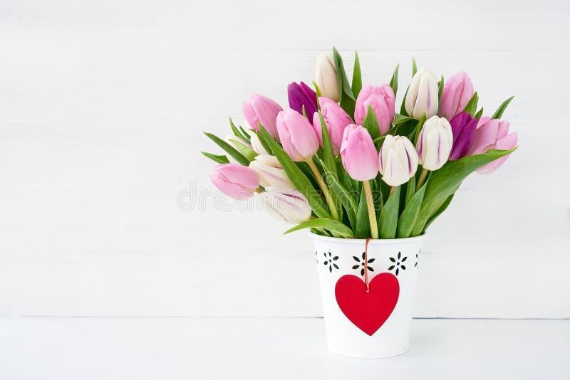 Ρόδινη και άσπρη ανθοδέσμη τουλιπών στο άσπρο βάζο που διακοσμείται με την κόκκινη καρδιά ανασκόπησης η μπλε κιβωτίων καρδιά δώρω στοκ εικόνες
