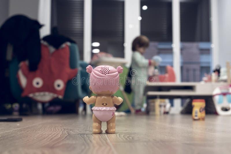 Ρόδινη κούκλα παιχνιδιών που περιμένει σε ένα θολωμένο σαλόνι εσωτερικό στοκ εικόνες με δικαίωμα ελεύθερης χρήσης