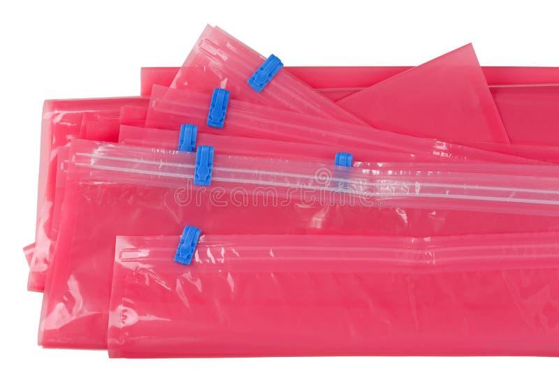 Ρόδινη πλαστική τσάντα κλειδαριών φερμουάρ με την μπλε σφράγιση στα υφάσματα καταστημάτων πακέτων στοκ εικόνες