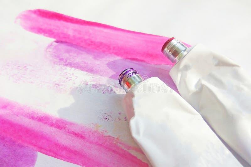 Ρόδινοι ακρυλικοί σωλήνες χρωμάτων και συρμένη χέρι αφηρημένη ροδανιλίνης εικόνα σχεδίων watercolor στο άσπρο κατασκευασμένο υπόβ στοκ φωτογραφία