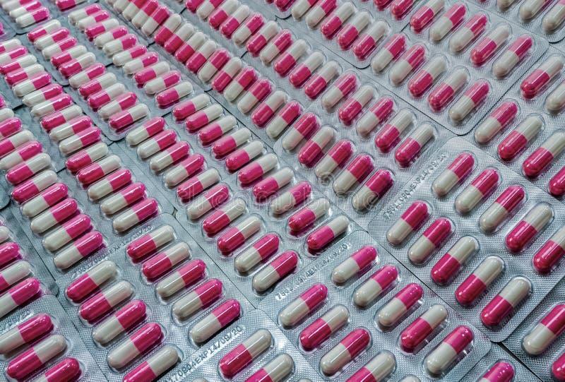 Ρόδινος-άσπρα αντιβιοτικά χάπια καψών κινηματογραφήσεων σε πρώτο πλάνο στο πακέτο φουσκαλών Αντιβιοτική αντίσταση φαρμάκων Βιομηχ στοκ φωτογραφία