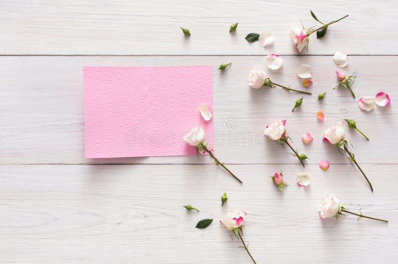 Ρόδινος αυξήθηκε λουλούδια και πέταλα στην άσπρη αγροτική ξύλινη, ανοικτή κενή ευχετήρια κάρτα στοκ φωτογραφία με δικαίωμα ελεύθερης χρήσης