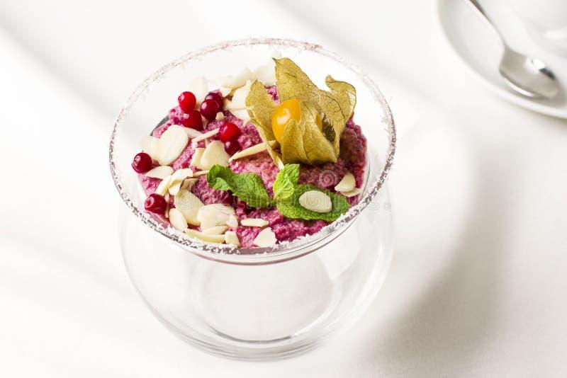 Ρόδινο ακατέργαστο mousse επιδορπίων παγωτό με τα μούρα και τα καρύδια στο γυαλί στοκ εικόνα με δικαίωμα ελεύθερης χρήσης