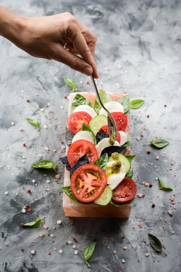 Ρόδινο αλατισμένο μαγείρεμα φραγμών Himalayan Η λεπτή γυναικών σάλτσα pesto χεριών χύνοντας στη caprese σαλάτα εξυπηρέτησε στον α στοκ φωτογραφία