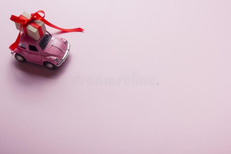Ρόδινο αναδρομικό αυτοκίνητο παιχνιδιών που παραδίδει το κιβώτιο δώρων στο υπόβαθρο κρητιδογραφιών Τοπ όψη στοκ φωτογραφία