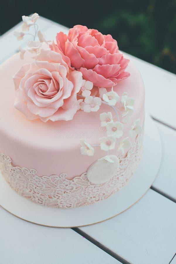 Ρόδινο γαμήλιο κέικ με τα τριαντάφυλλα παγώματος και ζάχαρης κοντά επάνω στοκ φωτογραφία με δικαίωμα ελεύθερης χρήσης