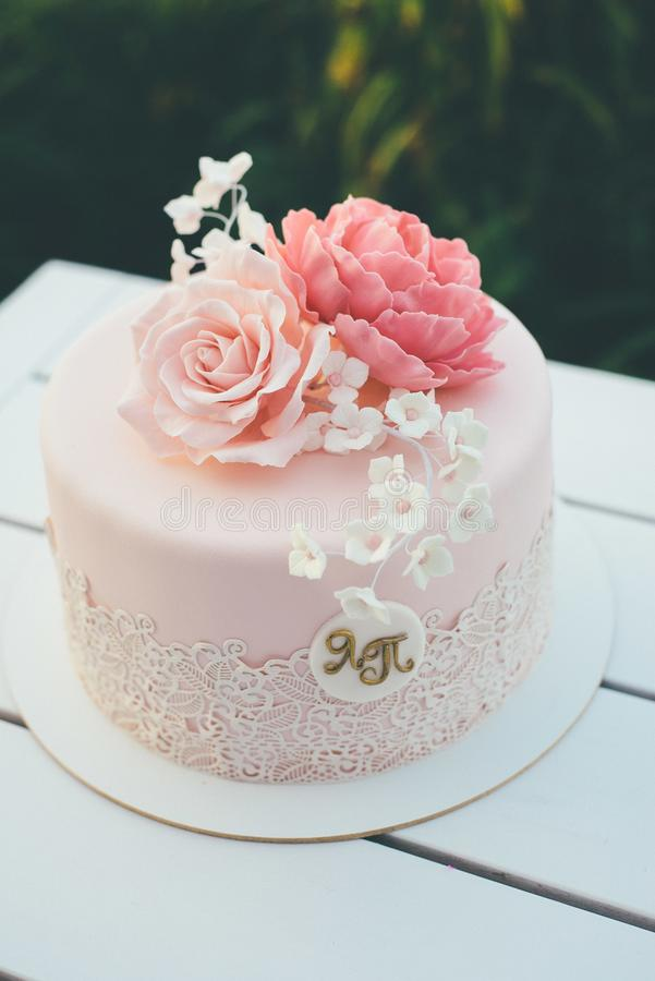 Ρόδινο γαμήλιο κέικ με τα τριαντάφυλλα παγώματος και ζάχαρης κοντά επάνω στοκ εικόνα με δικαίωμα ελεύθερης χρήσης