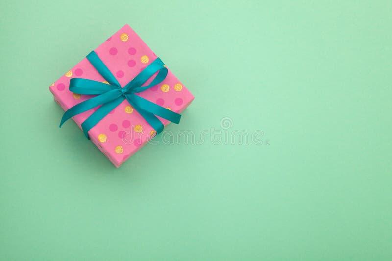Ρόδινο κιβώτιο δώρων εγγράφου τεχνών με ως παρόν για τα Χριστούγεννα, το νέο έτος, την ημέρα βαλεντίνων ή την επέτειο στο πράσινο στοκ φωτογραφία με δικαίωμα ελεύθερης χρήσης