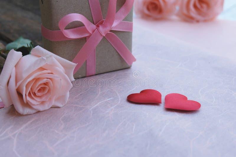 Ρόδινο κιβώτιο δώρων κορδελλών, πορτοκαλής-ρόδινα τριαντάφυλλα και κόκκινες καρδιές σατέν στον εκλεκτής ποιότητας ξύλινο πίνακα γ στοκ εικόνα