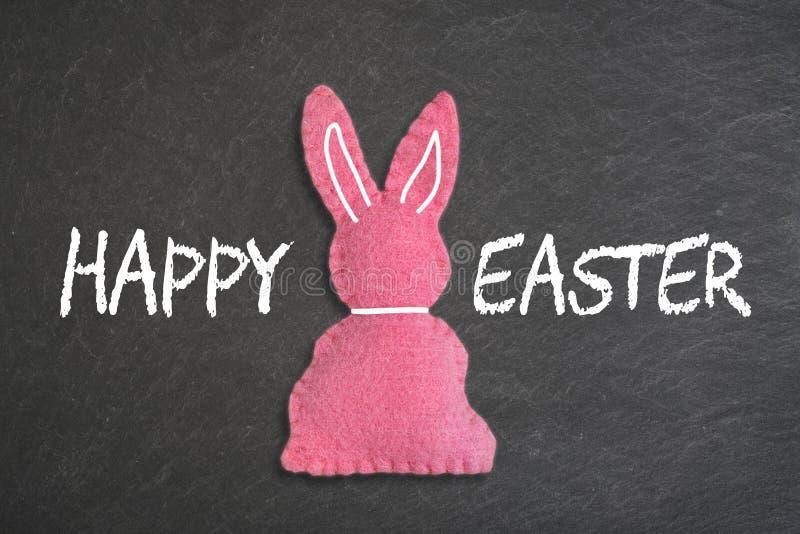 """Ρόδινο λαγουδάκι Πάσχας με το κείμενο """"ευτυχές Πάσχα """"σε ένα υπόβαθρο πινάκων κιμωλίας στοκ φωτογραφία με δικαίωμα ελεύθερης χρήσης"""