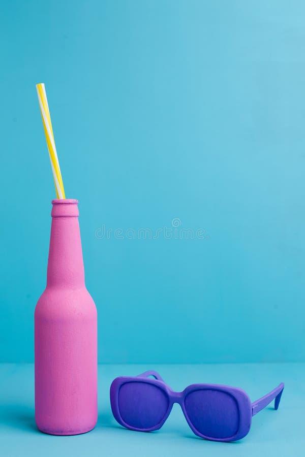 Ρόδινο μπουκάλι με το άχυρο κοκτέιλ στο μπλε υπόβαθρο, διάστημα αντιγράφων στοκ εικόνα με δικαίωμα ελεύθερης χρήσης