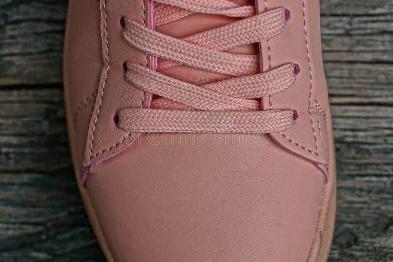 Ρόδινο πάνινο παπούτσι δέρματος με στον γκρίζο πίνακα στοκ φωτογραφία