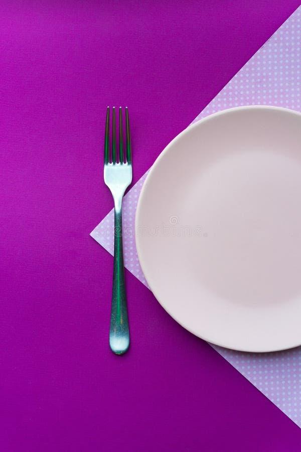 Ρόδινο πιάτο σε ένα ρόδινο τραπεζομάντιλο στοκ εικόνα