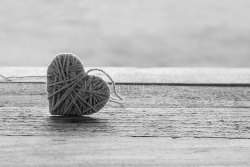 ρόδινο πλέκοντας μαλλί στη μορφή της καρδιάς εκλεκτής ποιότητας σε ξύλινο με το boke στοκ φωτογραφίες με δικαίωμα ελεύθερης χρήσης