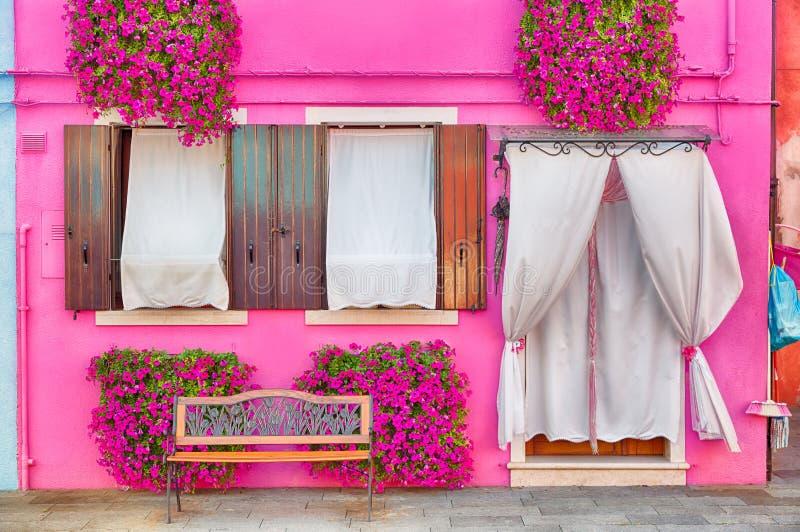Ρόδινο σπίτι με τα ρόδινες λουλούδια και τις εγκαταστάσεις Πάγκος της Νίκαιας κάτω από τα παράθυρα Ζωηρόχρωμο σπίτι στο νησί Bura στοκ εικόνα με δικαίωμα ελεύθερης χρήσης