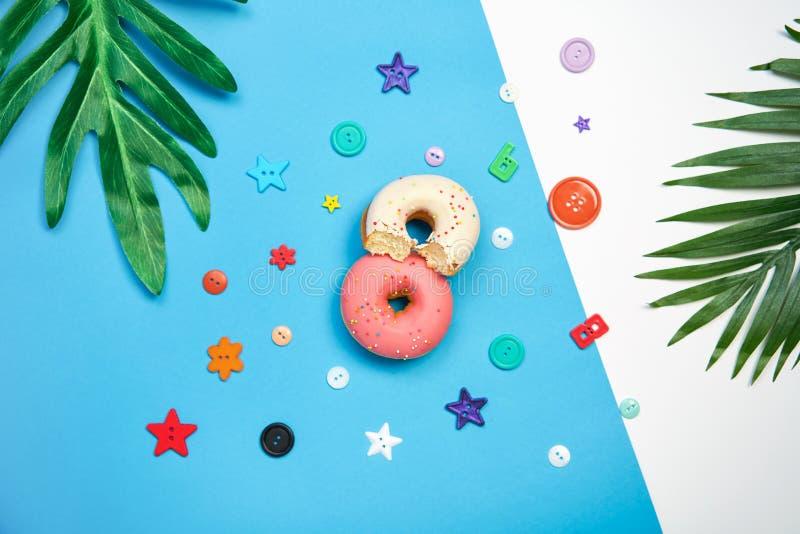 Ρόδινο doughnut και ζωηρόχρωμος σε ένα μπλε υπόβαθρο δημιουργικός μινιμαλισμός τροφίμων, κατάστημα καραμελών έννοιας στοκ εικόνα με δικαίωμα ελεύθερης χρήσης