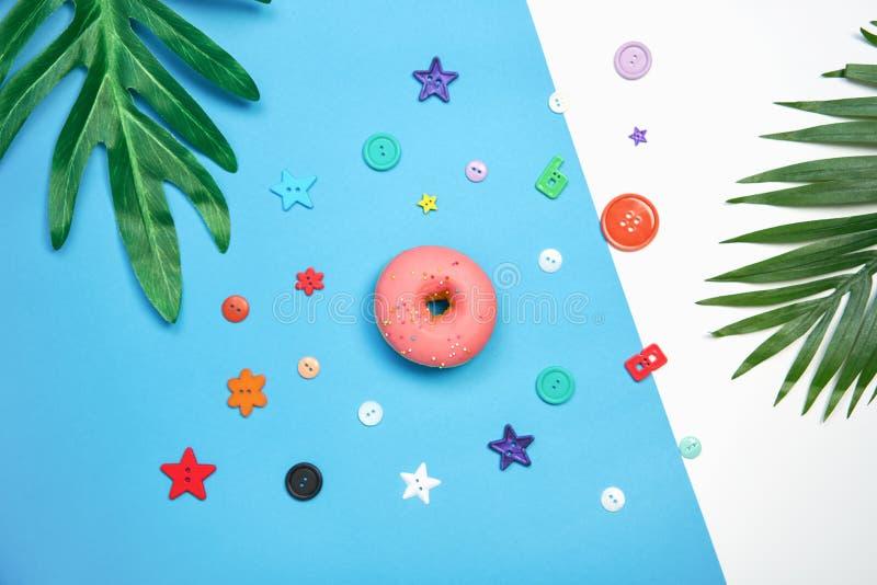 Ρόδινο doughnut και ζωηρόχρωμος σε ένα μπλε υπόβαθρο δημιουργικός μινιμαλισμός τροφίμων στοκ εικόνες με δικαίωμα ελεύθερης χρήσης