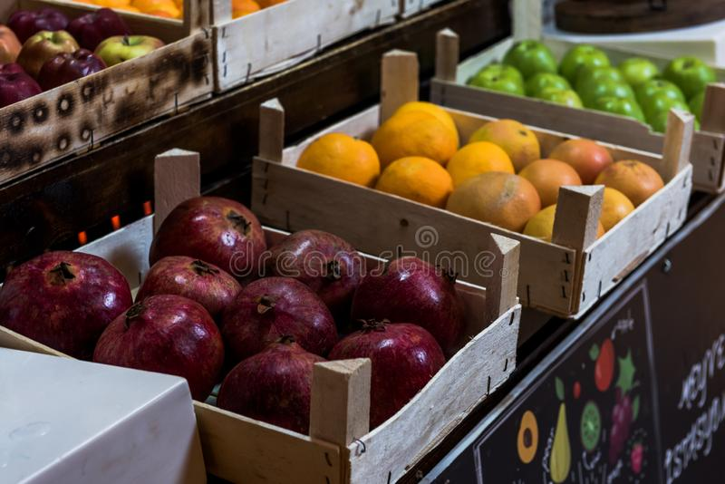 Ρόδι, πορτοκάλι και μήλα σε ξύλινες περιπτώσεις στοκ φωτογραφία