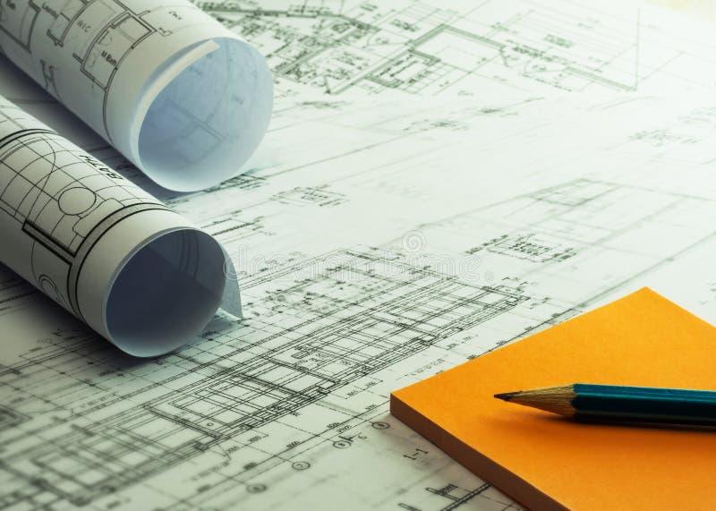 Ρόλοι και σχέδια αρχιτεκτόνων με τις πορτοκαλιά κολλώδη σημειώσεις και το μολύβι Α στοκ εικόνες με δικαίωμα ελεύθερης χρήσης
