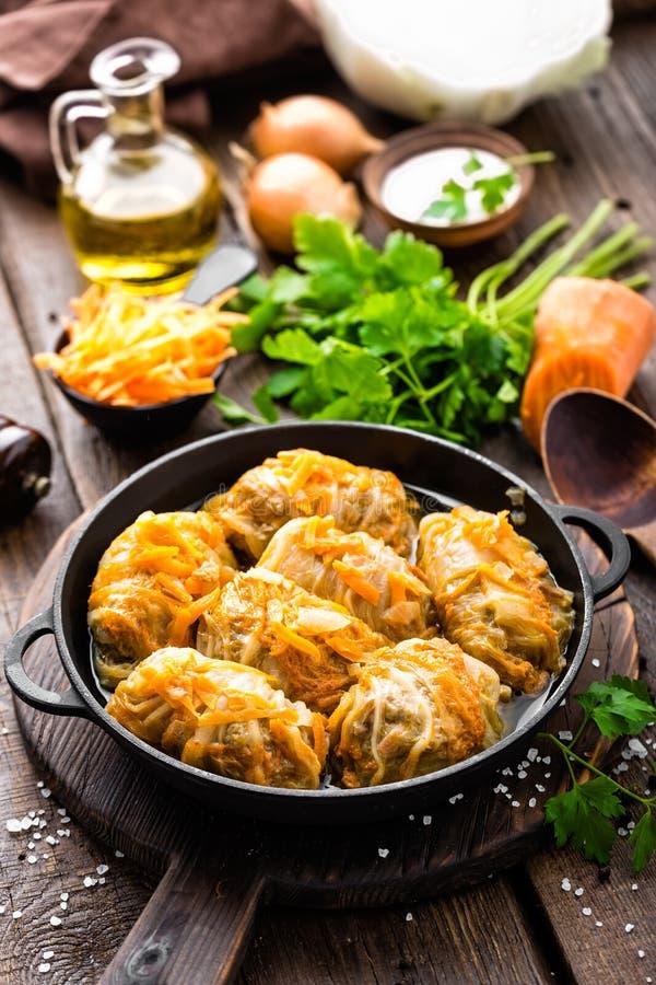 Ρόλοι λάχανων που μαγειρεύονται με το κρέας και τα λαχανικά στο τηγάνι στο σκοτεινό ξύλινο υπόβαθρο στοκ εικόνα με δικαίωμα ελεύθερης χρήσης