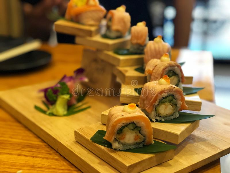 Ρόλοι σουσιών σολομών που τίθενται στο ξύλινο πιάτο Φρέσκα και εύγευστα ιαπωνικά τρόφιμα σουσιών στοκ φωτογραφία με δικαίωμα ελεύθερης χρήσης