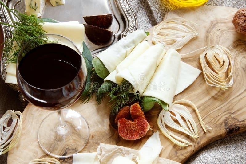 Ρόλοι του λεπτού τυριού Suluguni τηγανιτών με τον άνηθο και του σπανακιού σε έναν όμορφο πίνακα φιαγμένο από φυσικό ξύλο ελιών Δι στοκ φωτογραφίες