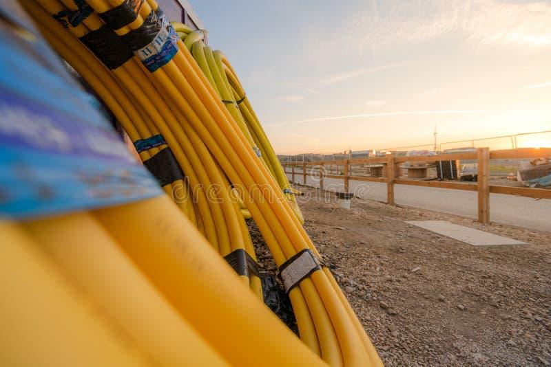 Ρόλοι των πλαστικών και λαστιχένιων σωλήνων και των σωλήνων που τοποθετούνται ενάντια σε έναν τοίχο μέσα σε ένα εργοτάξιο οικοδομ στοκ φωτογραφία με δικαίωμα ελεύθερης χρήσης