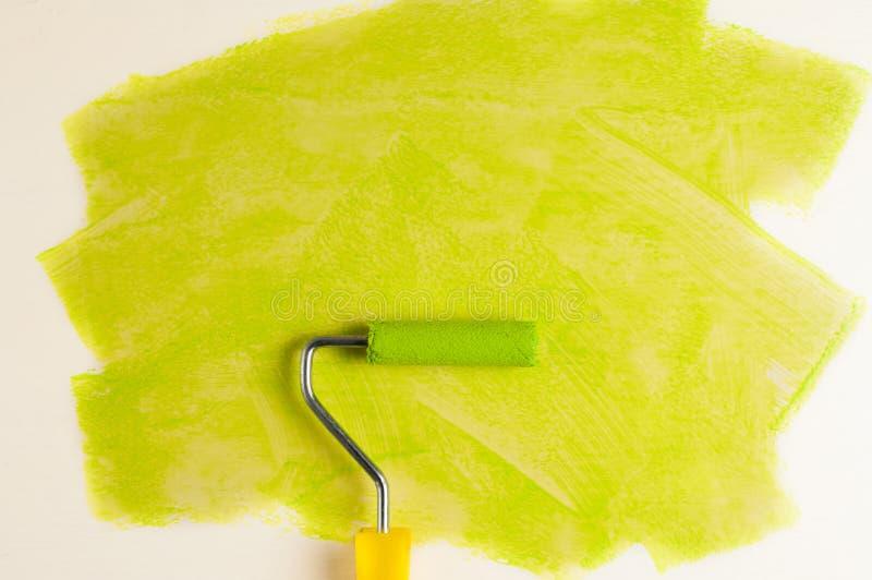 Ρόλος για το χρώμα και πράσινη διαδρομή στον τοίχο Έννοια επισκευής στοκ εικόνα