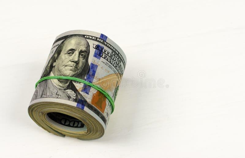 Ρόλος δολαρίων που σφίγγεται με τη ζώνη Κυλημένα χρήματα που απομονώνονται στο λευκό στοκ εικόνες