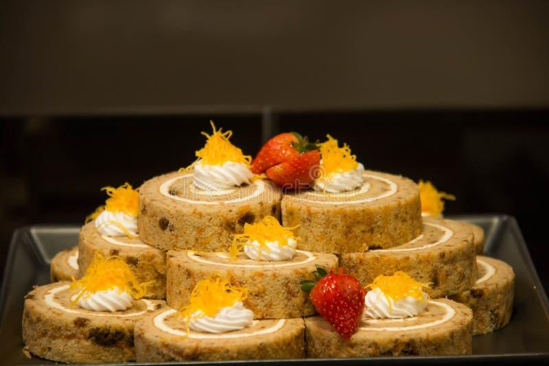 Ρόλος κέικ σφουγγαριών με την κρέμα στο πιάτο στοκ εικόνες