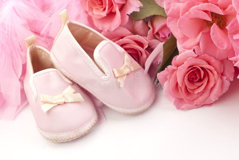 Ρόδινα παπούτσια και τριαντάφυλλα μωρών στοκ φωτογραφία