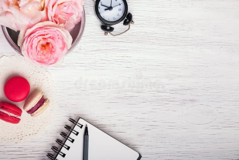 Ρόδινα τριαντάφυλλα, σημειωματάριο, ρολόι και macarons στοκ εικόνα