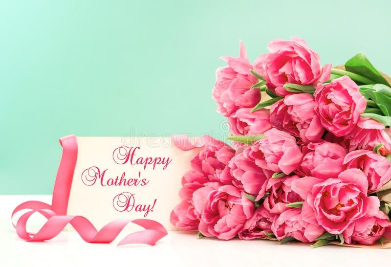 Ρόδινες τουλίπες και ευχετήρια κάρτα ευτυχείς μητέρες ημέρας στοκ εικόνες
