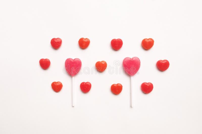 Ρόδινη μικρή κόκκινη καραμέλα μορφής καρδιών ημέρας βαλεντίνων ` s lollipop στο χαριτωμένο σχέδιο στο κενό υπόβαθρο της Λευκής Βί στοκ εικόνες