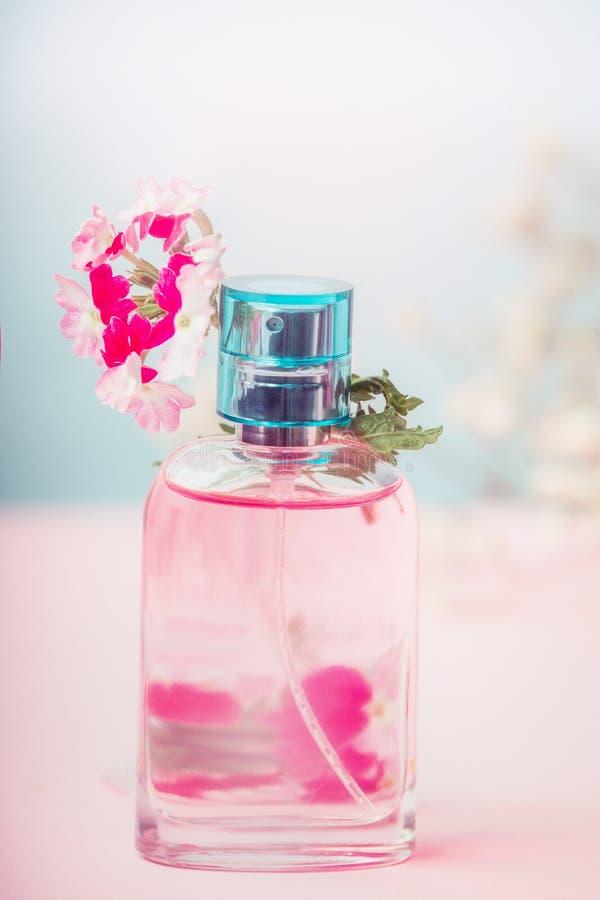 Ρόδινο μπουκάλι του floral αρώματος με τα λουλούδια, το φυσικό καλλυντικό προϊόν ή την έννοια ομορφιάς στο υπόβαθρο κρητιδογραφιώ στοκ φωτογραφία με δικαίωμα ελεύθερης χρήσης