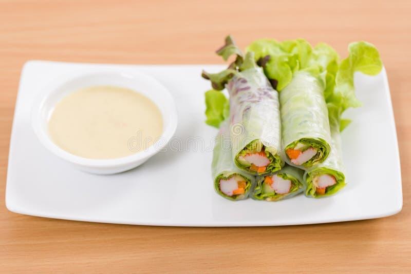 Ρόλοι σαλάτας και σάλτσα κρέμας στο άσπρο πιάτο και τον ξύλινο πίνακα στοκ φωτογραφία
