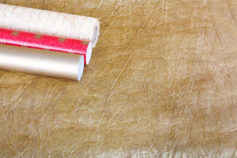 Ρόλοι του πολύχρωμου τυλίγοντας εγγράφου με την ταινία για τα δώρα επάνω στοκ εικόνα