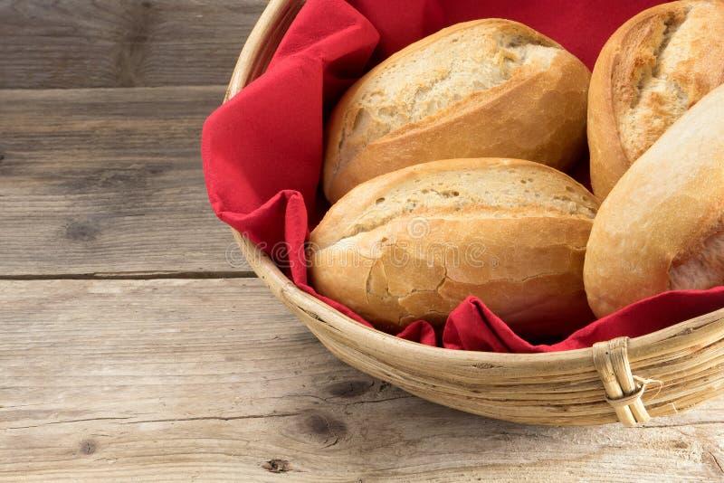 Ρόλοι ψωμιού σε ένα καλάθι με την κόκκινη πετσέτα στο παλαιό ξύλο στοκ εικόνα με δικαίωμα ελεύθερης χρήσης