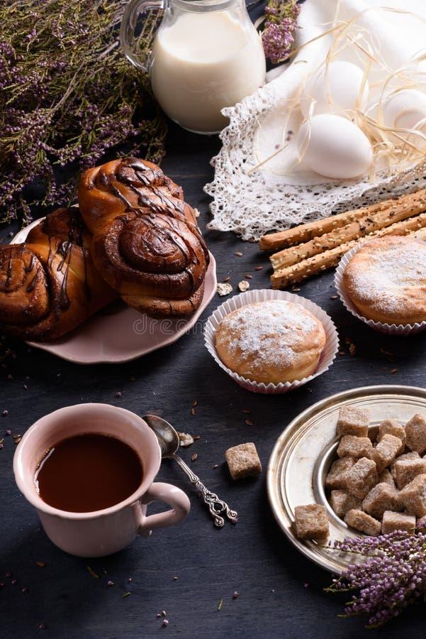 Ρόλοι, cupcakes, αυγά και κακάο σοκολάτας δανικοί Πρόγευμα που εξυπηρετείται στον ξύλινο πίνακα, που διακοσμείται με την ερείκη στοκ εικόνα με δικαίωμα ελεύθερης χρήσης