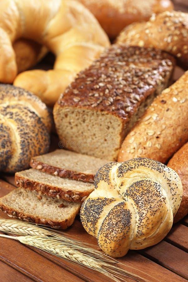 Ρόλος ψωμιού Kaiser με τους σπόρους παπαρουνών στον ξύλινο πίνακα στοκ φωτογραφία με δικαίωμα ελεύθερης χρήσης