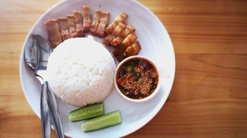 Ρύζι και τριζάτο χοιρινό κρέας με την εγγενή πηγή στοκ εικόνες