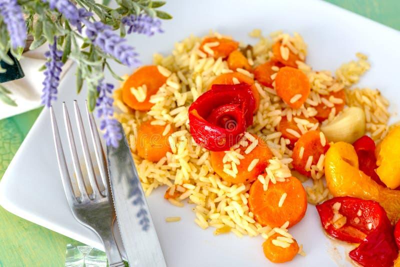 Ρύζι, καρότα και κόκκινα κίτρινα τηγανισμένα γλυκά πιπέρια σε ένα άσπρο κεραμικό πιάτο σε έναν ξύλινο πίνακα στοκ εικόνα με δικαίωμα ελεύθερης χρήσης