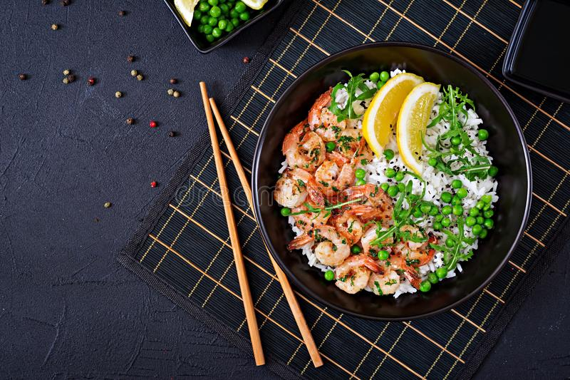 Ρύζι με τα νέα πράσινα μπιζέλια, τις γαρίδες και το arugula στο μαύρο κύπελλο στοκ εικόνα με δικαίωμα ελεύθερης χρήσης
