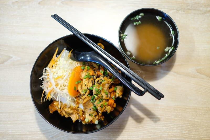 Ρύζι με το ψημένο στη σχάρα teriyaki χοιρινού κρέατος και κρεμμύδι άνοιξη στην κορυφή στο β στοκ εικόνες