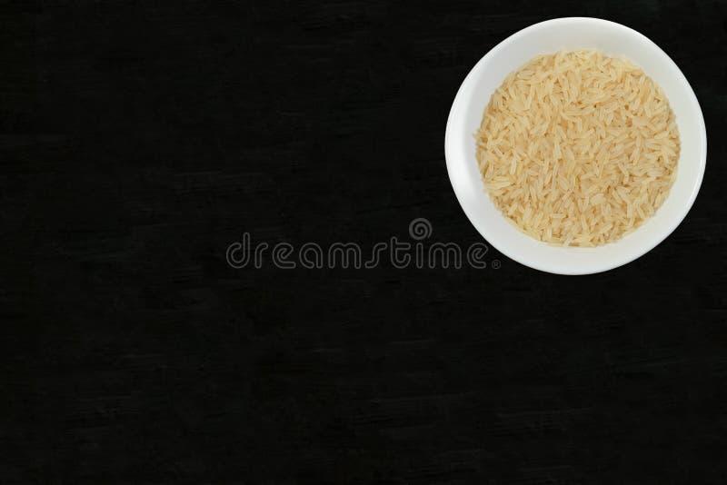Ρύζι στο άσπρο κύπελλο στο μαύρο υπόβαθρο, τοπ άποψη διαστημικό κείμενό σας στοκ εικόνες