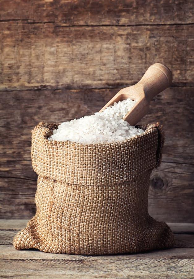 Ρύζι burlap στο σάκο με τη σέσουλα στο ξύλινο υπόβαθρο στοκ φωτογραφία