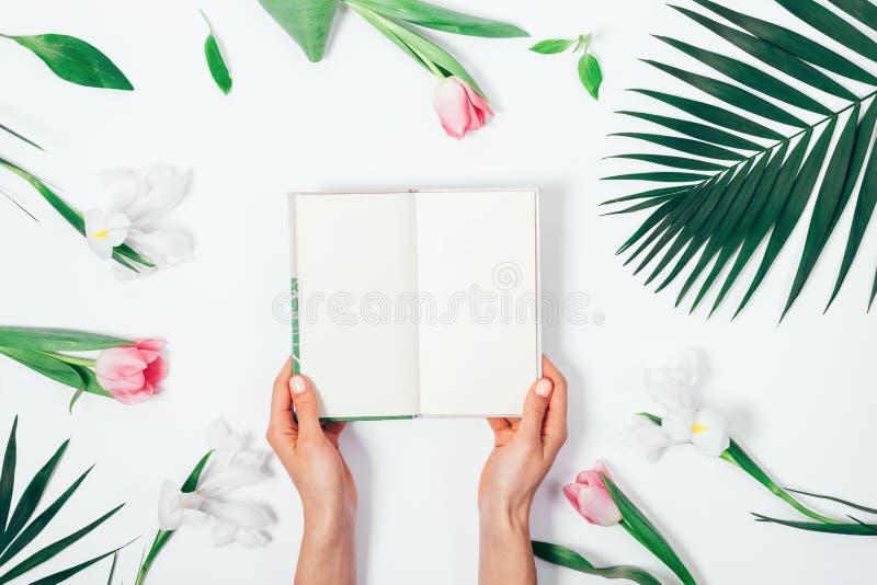Ρύθμιση λουλουδιών και ένα ανοικτό βιβλίο στοκ φωτογραφίες