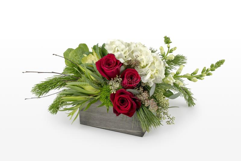 Ρύθμιση λουλουδιών Χριστουγέννων με τα κόκκινα τριαντάφυλλα και τα μικτά πράσινα διακοπών Επαγγελματικός floristry στοκ φωτογραφία