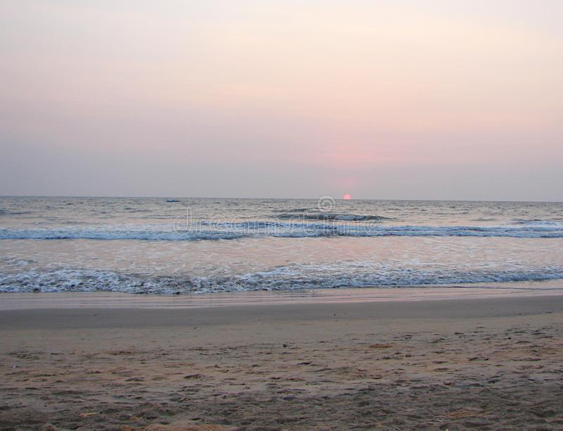 Ρύθμιση του κόκκινου ήλιου στον ορίζοντα πέρα από τη θάλασσα στην παραλία Payyambalam, Kannur, Κεράλα, Ινδία στοκ εικόνες με δικαίωμα ελεύθερης χρήσης